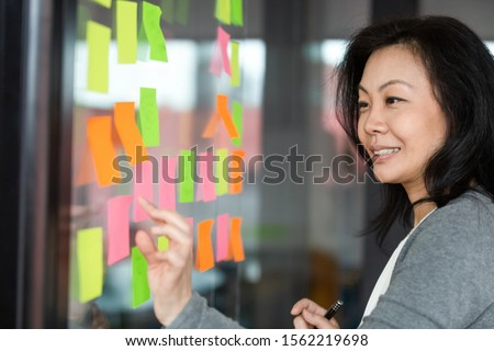 Side view head shot smiling middle aged korean female manager adding tasks on sticky notes on kanban board at office. Successful team leader managing configuring workflow, checking project progress.