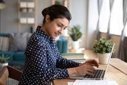 Side view head shot smiling young female indian student looking at paper notes, writing essay studying at home. Happy pleasant millennial woman freelancer working online on computer in living room.