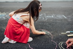 Side view image of little girl drawing with colorful chalks on playground. Child playing the summer's games outside. Kid drawing with chalk a heart on grey pavement. Activities for children.