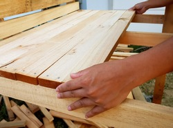 Side view image of man assembling wooden slats for making floor of kids playhouse in garden. Woodwork at house. Handmade wooden playhouse. Selective focus.