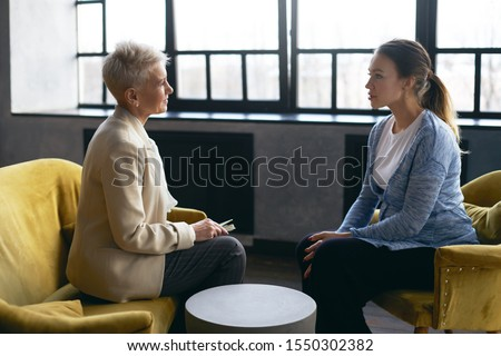 Side view image of middle aged female psychologist discusses the problems with young pregnant woman, sitting in armchairs, facing each other. Prenatal psychological therapy