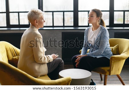 Side view image of two women sitting face to face in comfortable armchairs. Stylish mature female psychotherapist conducting counselling with young pregnant woman. Job interview and human resources