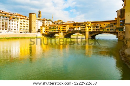 Side view in full sunlight of medieval stone bridge Ponte Vecchio over Arno river, Florence, Tuscany, Italy. stock photo