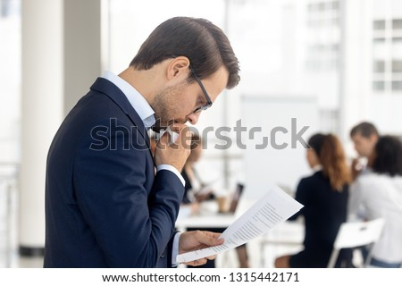 Side view insecure male holding paper reading preparing for performance feel afraid of public speaking, company staff sitting at desk in background. Fear of job interview fail, stress at work concept