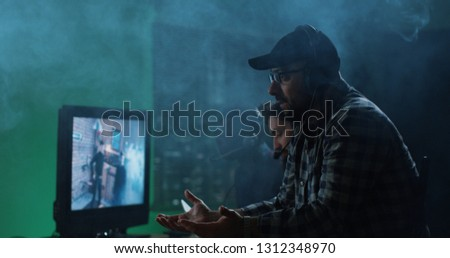 Side view man in headset producing film and yelling at workers on shooting stage #1312348970