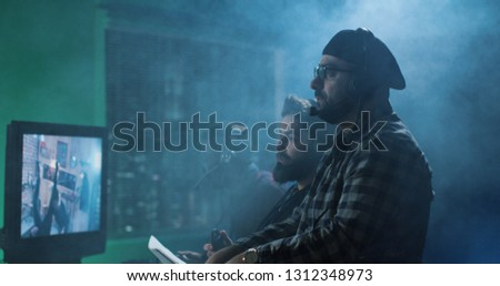 Side view man in headset producing film and yelling at workers on shooting stage