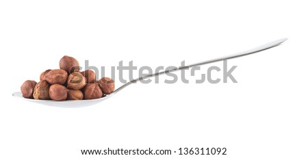 Side view metal spoon full of hazelnuts isolated over white background