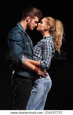 Side view of a attractive young couple holding each other, face to face, almost kissing.