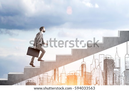 Side view of a bearded man carrying a suitcase and going up the stairs. There is a city panorama in the background and a cloudy sky.