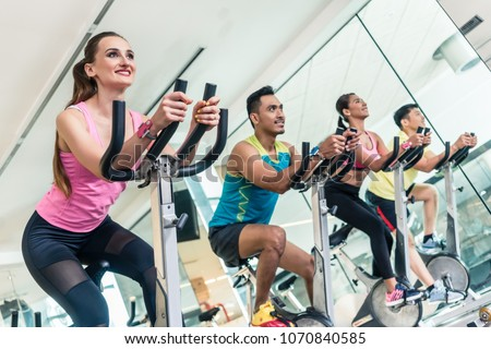 Side view of a beautiful fit young woman smiling while pedaling during cardio workout at indoor cycling group class in a modern fitness club  #1070840585
