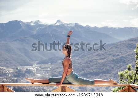 Side view of a beautiful flexible brave young woman athlete doing the splits while sitting on the railing of terrace with mountain views overgrown with greenery and shrubs on a warm summer day