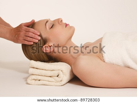 Side view of a beautiful mid adult woman receiving head massage against white background