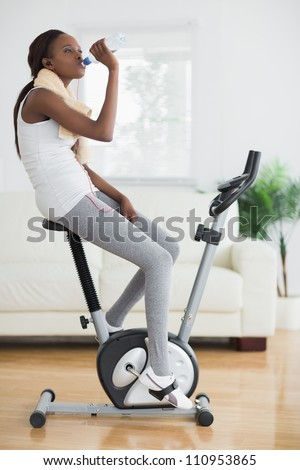 Side view of a black woman on an exercise bike in a living room