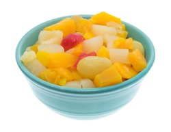 Side view of a bowl of canned fruit cocktail in a bowl isolated on a white background.