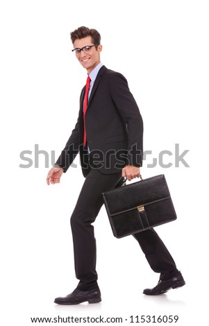 side view of a business man holding a briefcase and walking forward while looking at the camera