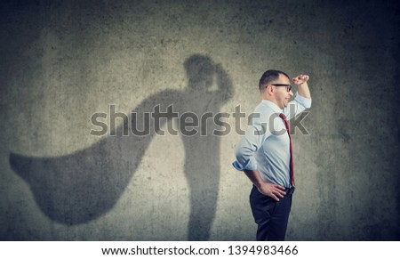 Side view of a business man imagining to be a super hero looking aspired. #1394983466