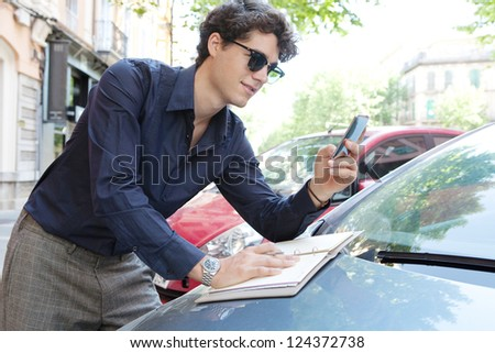 Side view of a businessman leaning on a car using a smart phone and taking notes in the city, wearing shades outdoors.