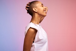 Side view of a carefree woman with shaved head. Confident female with short hair on colorful background.