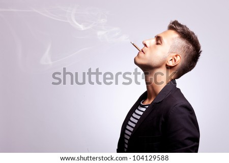 side view of a casual fashion man smoking a cigar on gray background