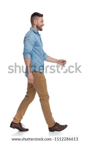 side view of a casual man with blue shirt walking and looking ahead happy on white studio background