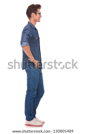 side view of a casual young man standing with his hands on his hips and looking away from the camera. isolated on a white background