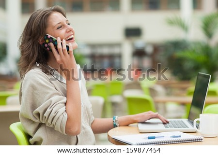 Side view of a cheerful female student using cellphone and laptop at cafeteria table