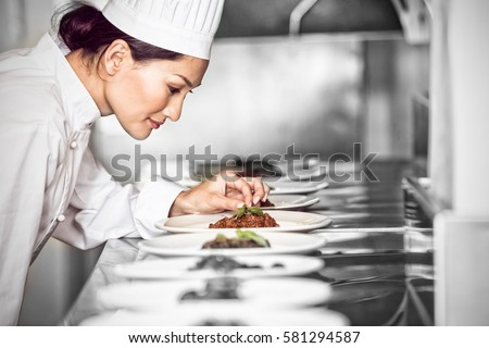 Side view of a concentrated female chef garnishing food in the kitchen #581294587