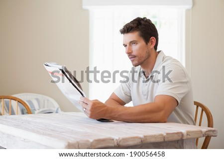 Side view of a concentrated young man reading newspaper at table