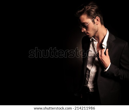 side view of a cool fashion man in suit and sunglasses pulling his collar and looking down