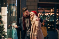 Side view of a couple looking through a store window while christmas shopping together.