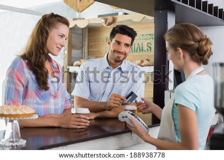 Side view of a couple paying bill at coffee shop using card bill #188938778