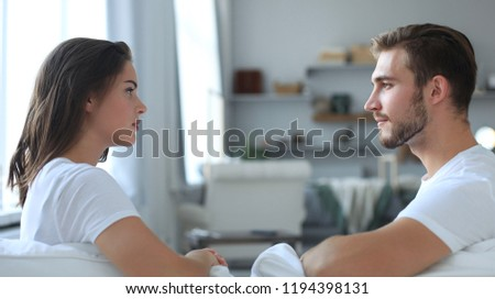 Side view of a couple talking sitting on a couch and looking each other at home. #1194398131