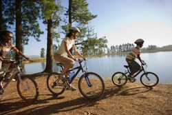Side view of a couple with their son mountain biking along a lakeside on a woodland trail on a sunny day.