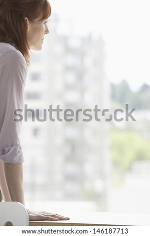Side view of a cropped businesswoman looking out of window