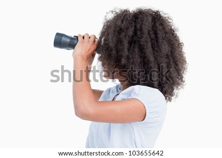 Side view of a curly woman looking with binoculars against a white background
