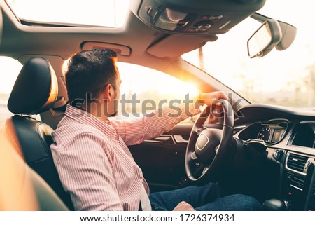 Side view of a driver sitting in comfortable new car with sunroof and looking out the window on sunset Foto stock ©