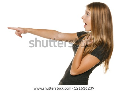 Side view of a excited casual female pointing out at copyspace, over white background