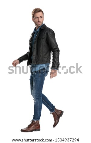 side view of a fine casual man with black leather jacket walking and looking back over his shoulder serious on white studio background