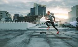 Side view of a fitness man running on rooftop using resistance parachute. Athlete training on rooftop running with a parachute tied to his waist.