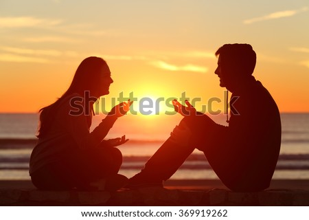 Side view of a full body of two friends or couple silhouette of teens sitting and talking at sunrise on the beach with the sun in the middle #369919262