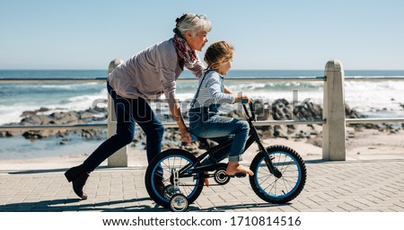 Side view of a girl riding a bicycle while her grandmother runs along holding the kid. Senior woman teaching a small girl to ride a bicycle on the road alongside the beach.