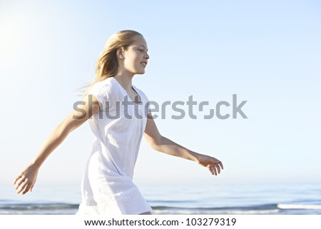 Side view of a girl walking along the shore on a beach with blue sky in the background.