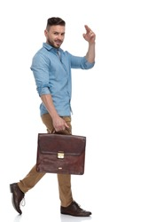 side view of a gorgeous casual man with blue shirt and briefcase walking and saluting on white studio background