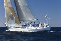 Side view of a group of crew members sitting on the side of a sailboat in the ocean against sky