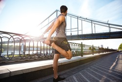 Side view of a handsome young sports man doing stretching leaning against bridge railing outdoors