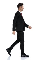 Side view of a happy businessman smiling while wearing a black suit and red tie, walking on white studio background