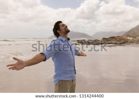 Side view of a happy Caucasian man standing with arms outstretched on the beach
