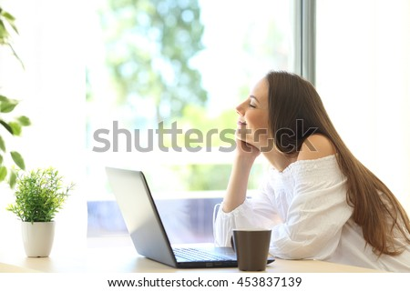 Side view of a happy girl with a laptop relaxing sitting near a window of a house interior