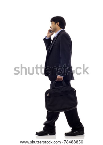 Side view of a happy Indian business man talking on the mobile phone isolated over white background