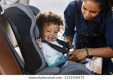 Side view of a happy little boy looking at camera while his mother buckling him in a car seat Сток-фото ©